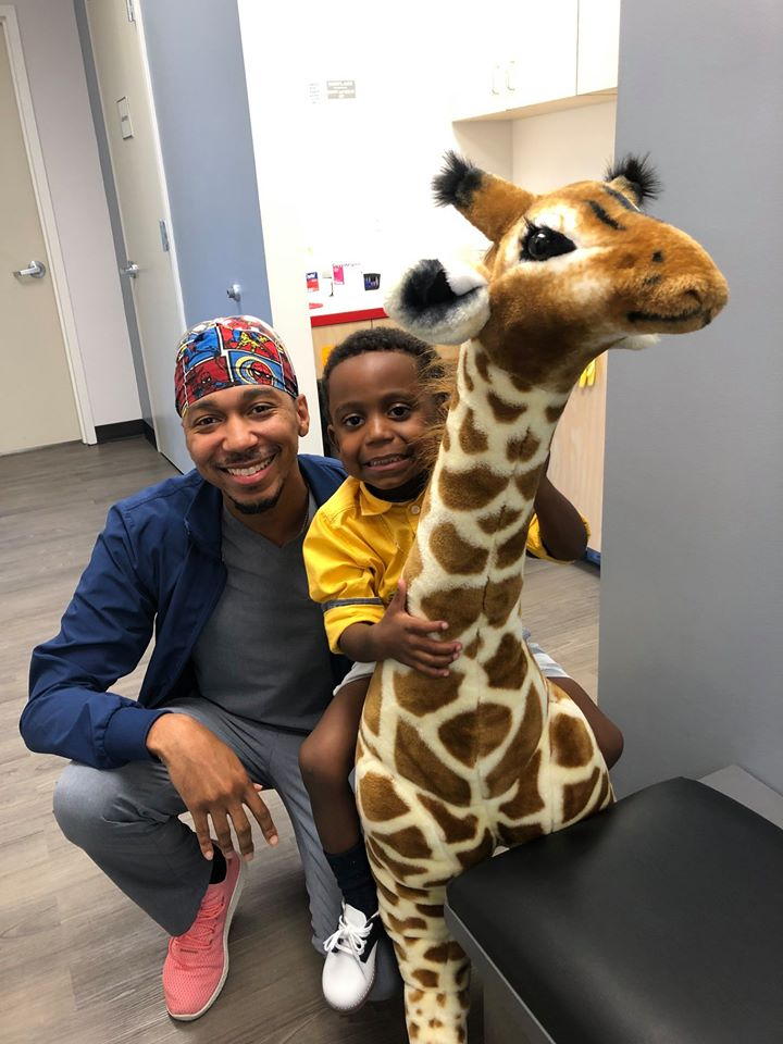 Dr. Jenkins poses with a young patient who is sitting on a giant stuffed toy giraffe.